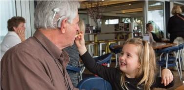Opa en kleindochter aan het eten. Opa draagt een Naída CI Q90 spraakprocessor in de kleur Silver Gray