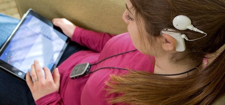 Naída CI Q90 spraakprocessor en zendspoel die het geluid ontvangen van een tablet via het Roger systeem